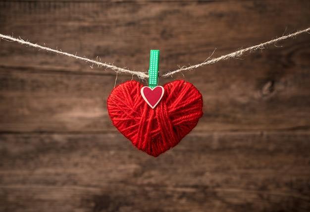 Un cœur rouge est suspendu à une corde par une pince à linge sur un bois.