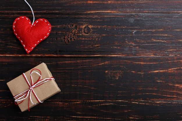 Coeur rouge en feutre et cadeau à la main sur une table en bois blanc, concept, bannière, espace de copie.