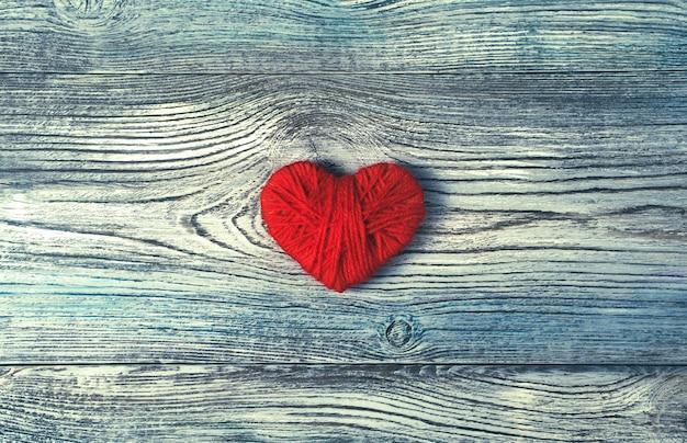 Un coeur rouge en fil sur un fond gris-bleu texturé en bois.