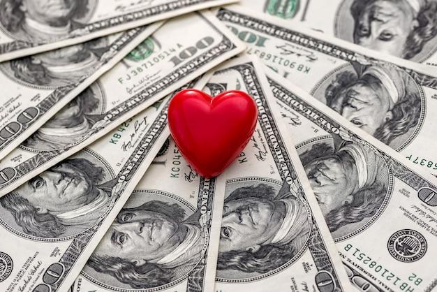 Coeur rouge sur fond de billets en dollars