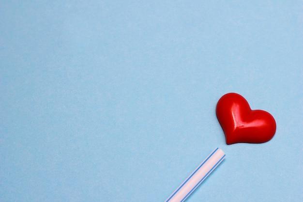 Un coeur rouge sur fond bleu près d'un tube à cocktail en plastique. concept de la saint-valentin. l'idée de l'amour. copiez l'espace.