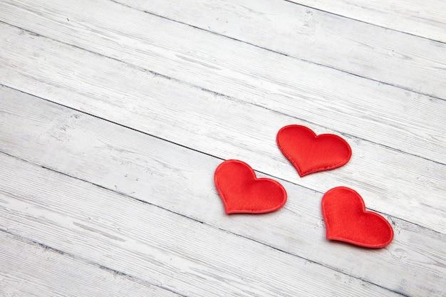 Coeur rouge sur fond en bois blanc.