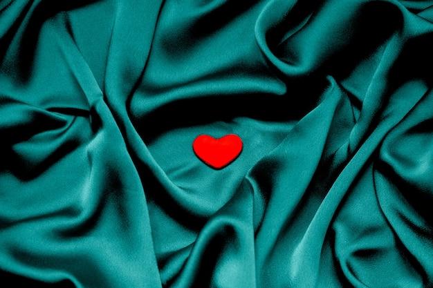 Coeur rouge sur fond de tissu. bleu vert