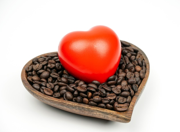 Coeur rouge avec des grains de café dans un bol en bois sur fond blanc pour l'idée de la saint-valentin