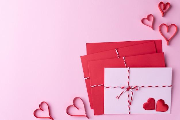 Cœur rouge et lettre rose rouge sur fond rose.