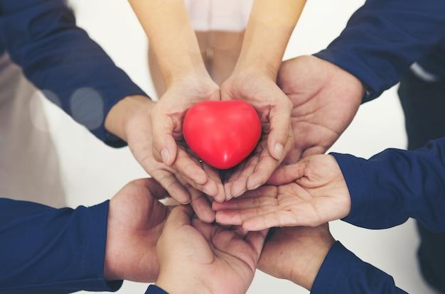 Coeur rouge sur les mains collaborent ensemble du travail d'équipe