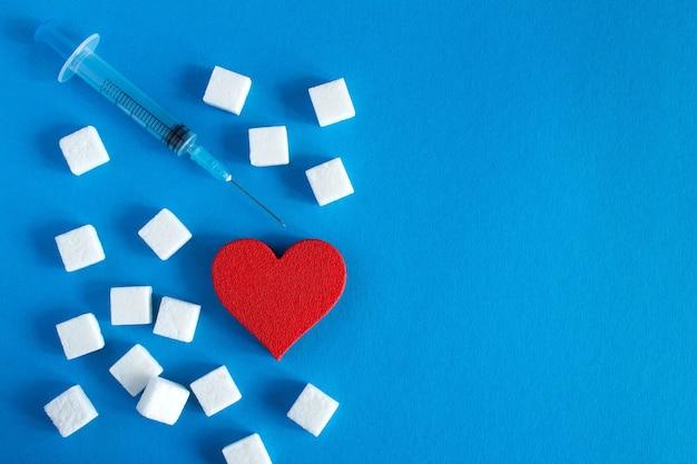 Coeur rouge avec des morceaux de sucre et une seringue