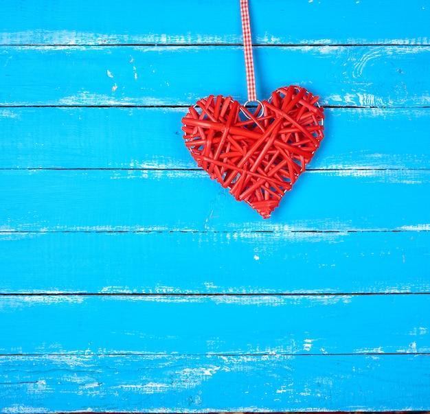 Coeur rouge en osier sur fond bleu