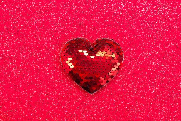 Coeur rouge avec des paillettes sur tissu rouge.