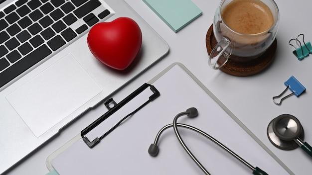 Coeur rouge, presse-papiers, ordinateur portable et stéthoscope sur fond blanc. concept d'assurance maladie.