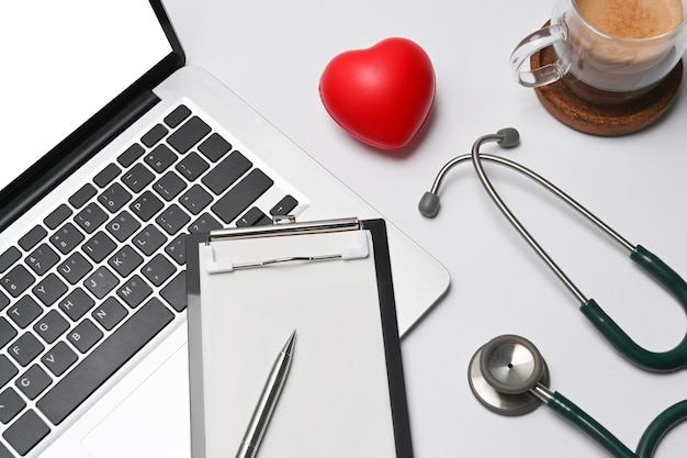 Coeur rouge, presse-papiers vide, ordinateur portable et stéthoscope sur l'espace de travail du médecin.