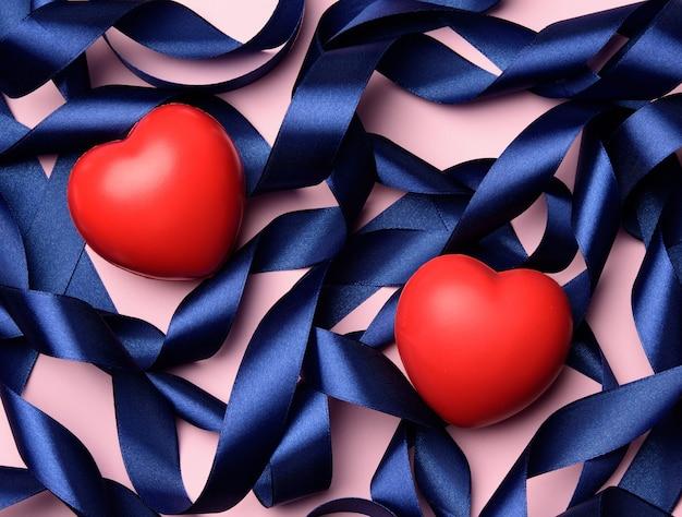 Coeur rouge et ruban enroulé de soie bleue sur une surface pinkd, saint valentin, vue de dessus