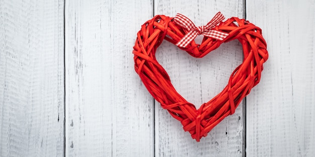 Coeur rouge de ruban sur fond en bois blanc, modèle avec espace de texte. mise à plat avec concept d'amour, carte de saint valentin, maquette. décoration de mise en page. cadre festif, bannière d'art. saint valentin - vacances.