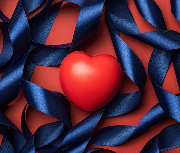 Coeur rouge et ruban frisé en soie bleue sur fond rouge, saint valentin, vue de dessus