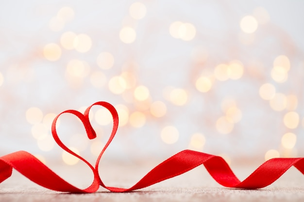 Coeur rouge ruban rouge forme de coeur fond bokeh