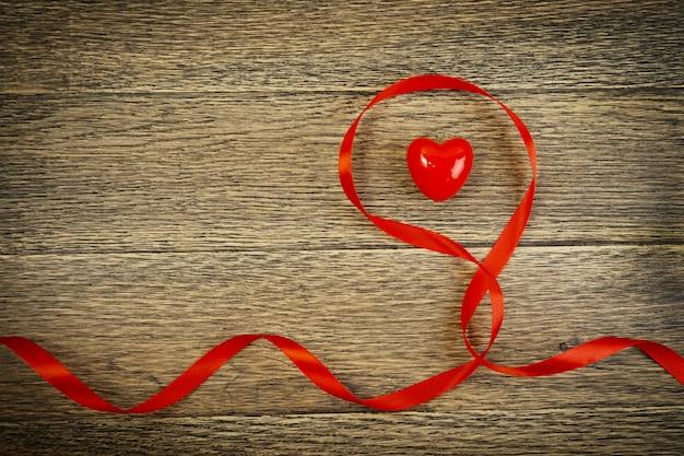 Coeur rouge saint valentin romantique et ruban écarlate sur la vue de dessus de fond en bois rustique ancien.