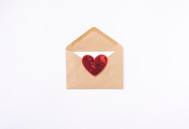 Un cœur rouge se trouve sur une enveloppe brune pour la saint valentin
