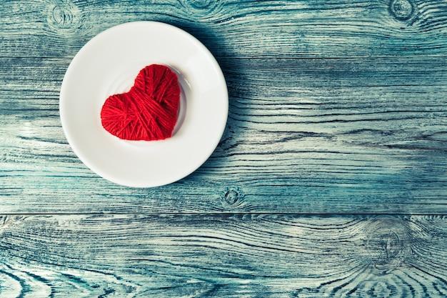 Coeur rouge sur une soucoupe blanche dans le coin supérieur gauche de la table sur un fond en bois.