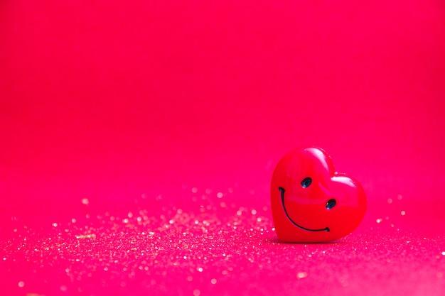 Coeur rouge souriant sur un espace de copie de fond rouge brillant
