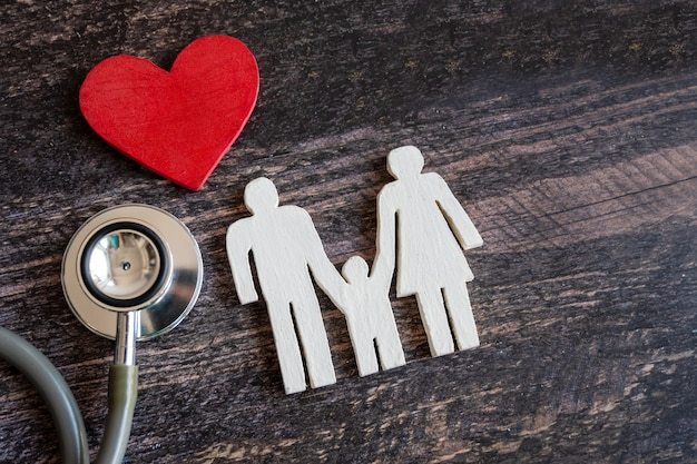Coeur rouge, stéthoscope et famille d'icônes sur le bureau en bois. concept d'assurance médicale
