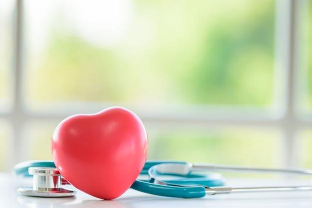 Coeur rouge et stéthoscope avec fenêtre le matin.