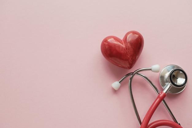 Coeur rouge avec stéthoscope sur fond rose