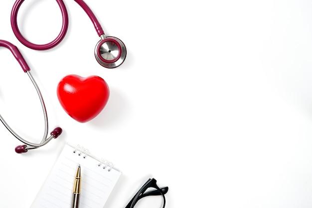 Coeur rouge avec stéthoscope et ordinateur portable sur fond blanc selective focus