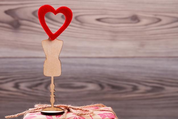 Coeur rouge sur support en bois. arc de corde et coeur. humeur positive le jour de la saint-valentin. souhaits de joie et d'amour.