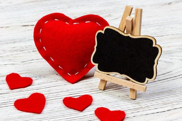 Un coeur rouge avec tableau noir et petits coeurs.