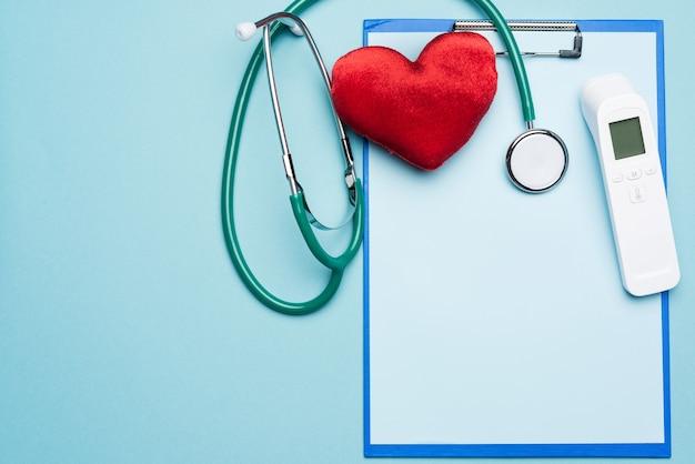 Coeur rouge, thermomètre électronique et autres fournitures médicales sur fond bleu, vue du dessus