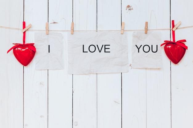 Coeur rouge et vieux papier avec du texte j'aime vous accroché au corde à linge sur fond blanc en bois.