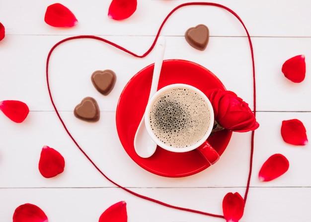 Coeur de ruban près de bonbons au chocolat, tasse de boisson sur une assiette et pétales