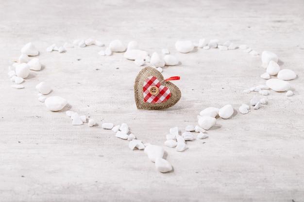 Coeur de saint valentin décoré de roches blanches sur fond de bois clair. vue de dessus, mise à plat. copier l'espace