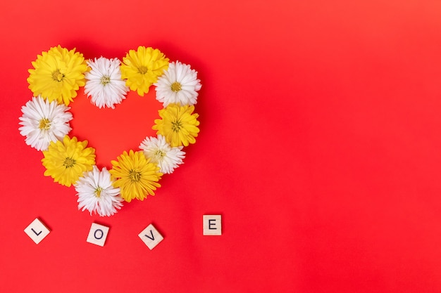Coeur saint valentin fait de belles fleurs isolés sur fond rouge. vue d'en-haut.