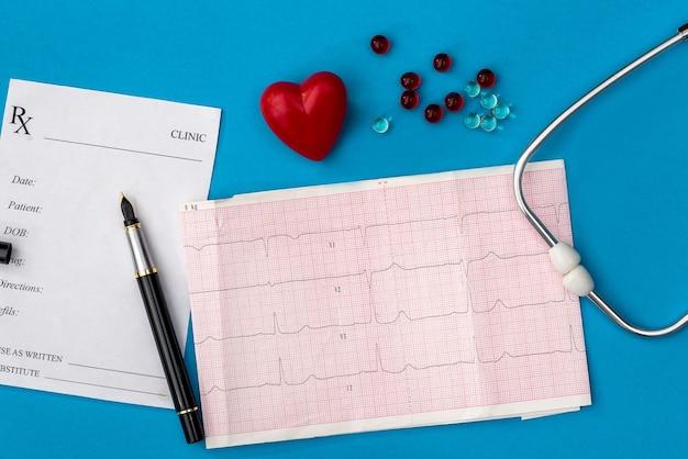 Coeur, stéthoscope, cardiogramme, reçu de pharmacie et comprimés sont mis en évidence sur un fond bleu
