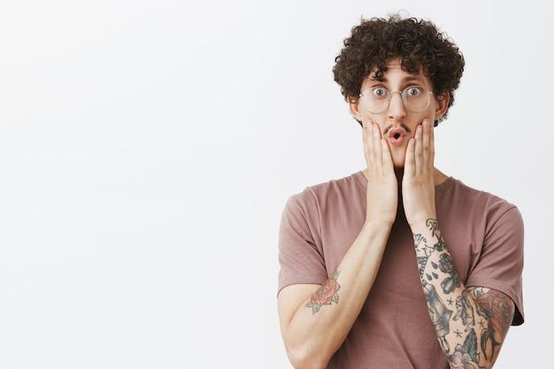 Cœur timide à l'intérieur d'apparence provoquante. inquiet mignon et expressif jeune mec juif avec des tatouages de moustache tenant les mains sur le visage pliant les lèvres avec empathie se sentant désolé pour kitty en difficulté