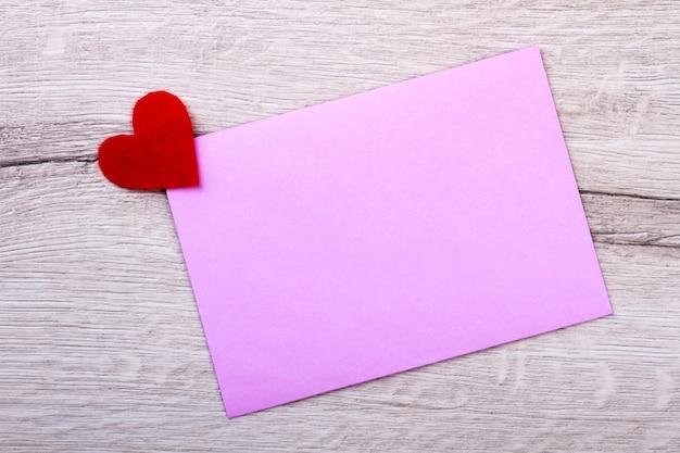 Coeur en tissu et carte papier. papier rose sur fond en bois. montrez le soin en utilisant la main. faites une surprise pour la petite amie.