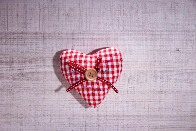 Coeur en tissu avec des épingles de couleur sur bois