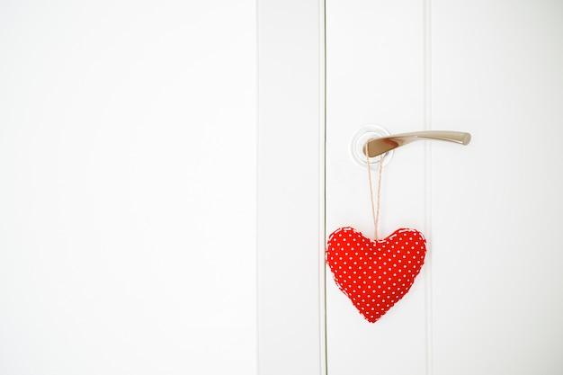 Coeur de tissu rouge accroché à la porte