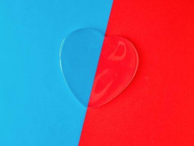 Coeur transparent sur fond bleu et rouge. un symbole d'amour et de vie.