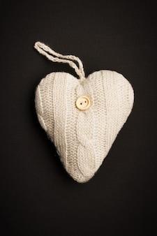Coeur tricoté avec bouton de couture dessus sur fond noir