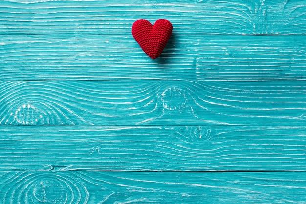 Cœur tricoté sur fond bleu en bois