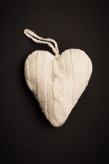 Coeur tricoté à la main sur fond noir