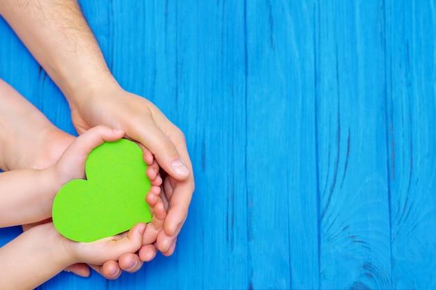 Coeur vert dans les mains de l'adulte et de l'enfant.