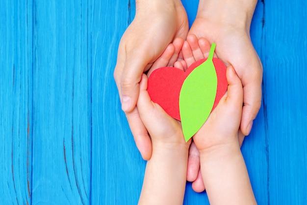 Coeur vert dans les mains de l'adulte et de l'enfant