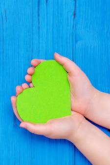 Coeur vert dans les mains de l'enfant