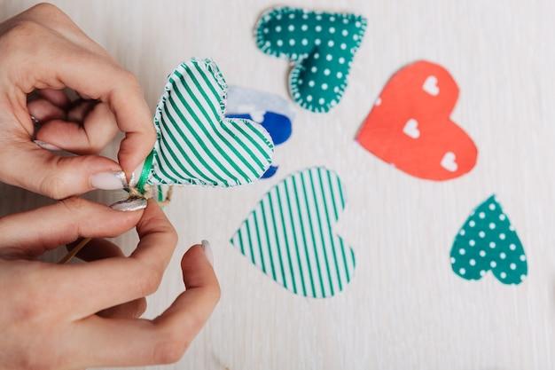 Coeur vert fait maison en tissu entre les mains.