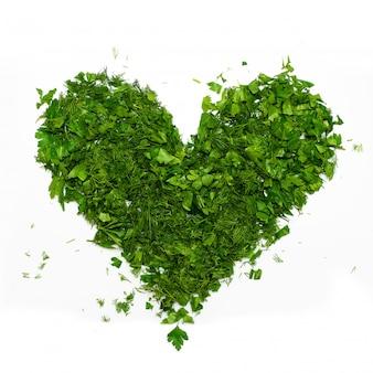 Un coeur vert de persil haché et d'aneth sur blanc