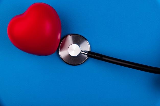 Coeur volumétrique avec un phonendoscope sur fond bleu. le concept de prise en charge des patients atteints de maladies cardiaques.