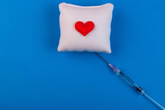 Coeur volumétrique avec une seringue sur fond bleu. le concept de prise en charge des patients atteints de maladies cardiaques.